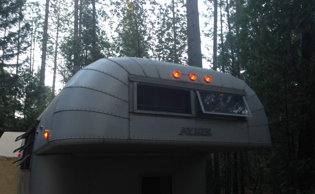 Vintage Avion camper with orange running lights on cabover and sides lighted.