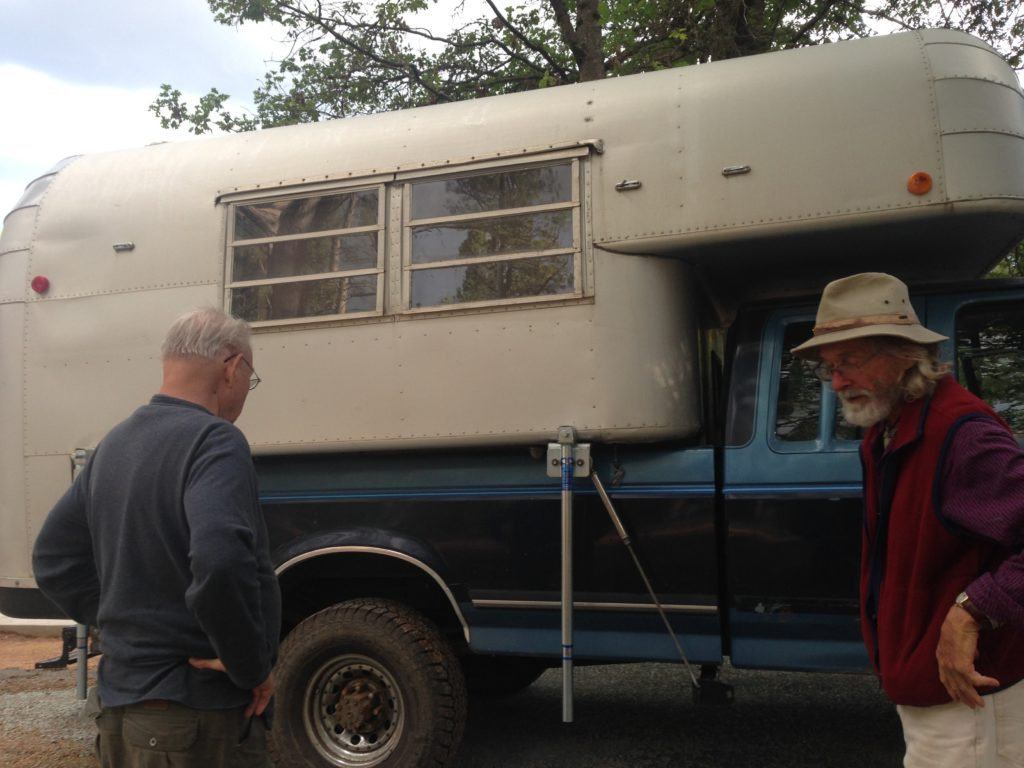 Two men examine the exterior of 1965 Avion camper.