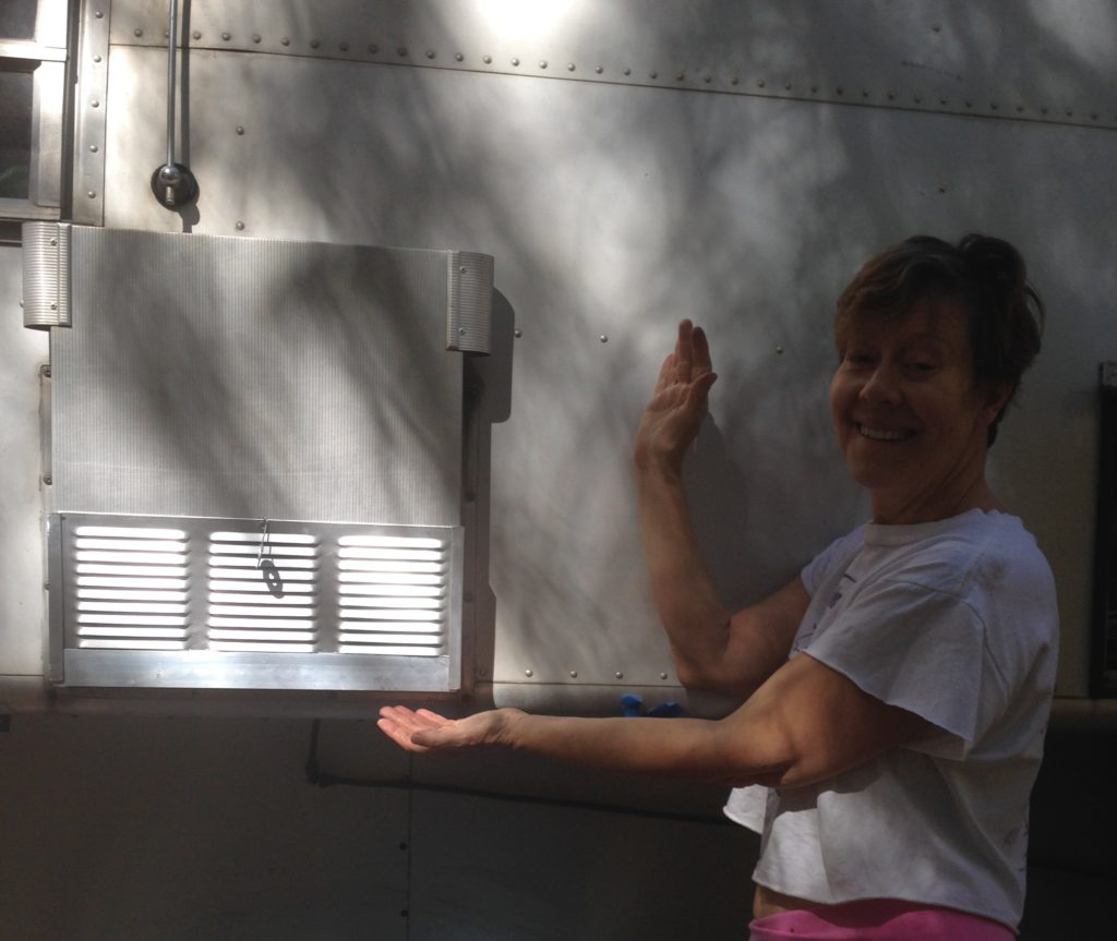 Jennifer demonstrates the new aluminum cover for the exterior access to the hot water heater on her 1965 Avion camper.
