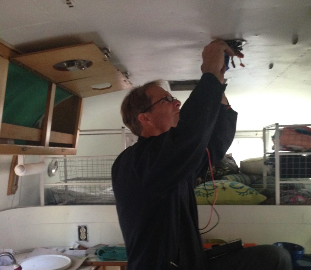 Man works on crazy tangle of wires emerging from ceiling light of vintage camper.
