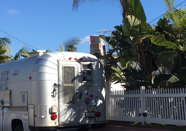 A photograph of The Avion camper parked alongside a white picket fence with big greenery.